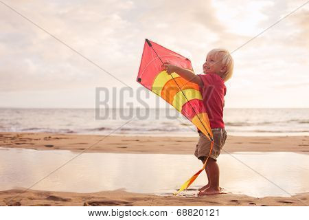 Happy young boy playing with kite on the beach at sunset