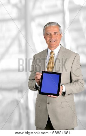 A mature businessman holding a tablet computer with blue screen facing forward. Easy to replace screen to add your own graphic. Vertical format against blurred modern office interior.
