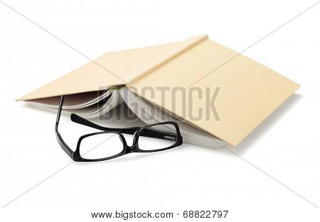 Spectacles Beside Inverted Book On White Background