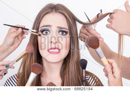 closeup of beautiful blond girl getting hair and makeup done