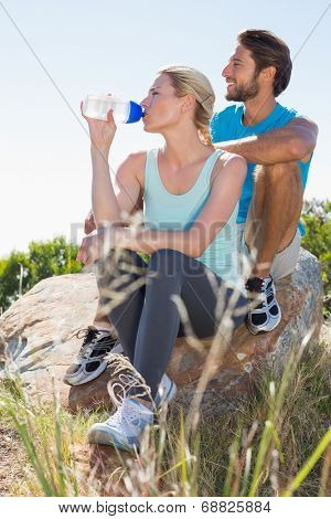 Fit couple taking a break at summit looking at the view on a sunny day