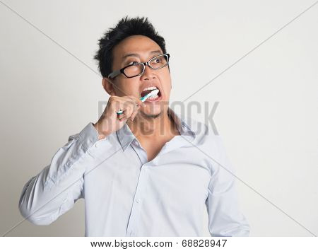 Asian business man woke up late, brushing teeth in hurry, on plain background