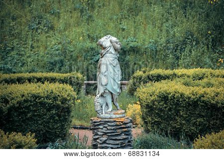 Headless statue of with a sheep in the garden
