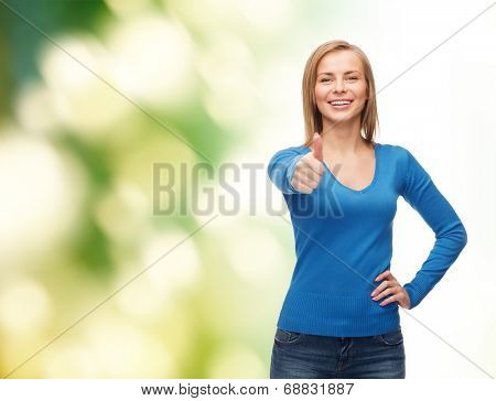 happiness, gesture and people concept - smiling young woman in casual clothes showing thumbs up