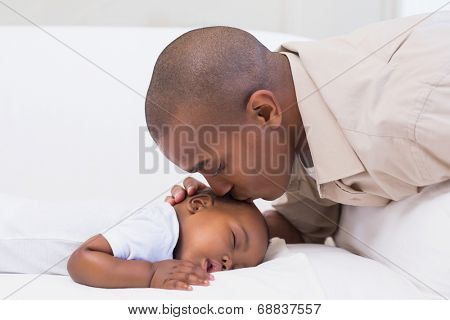 Adorable baby boy sleeping while being watched by father at home in the living room