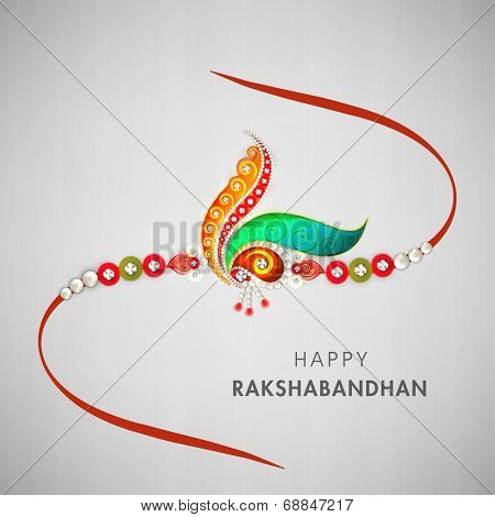 Beautiful rakhi decorated with peacock feathers and colorful pearls on grey background for Raksha Bandhan celebrations.