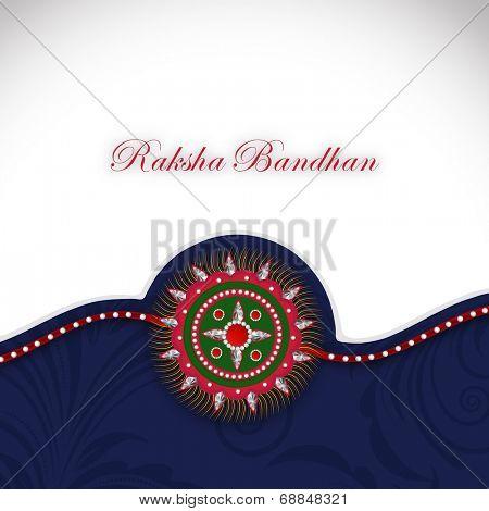 Beautiful Rakhi on grey and blue background on the occasion of Raksha Bandhan festival.