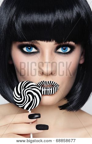 Conceptual portrait of young beautiful blue-eyed brunette with striped lips and fancy lollipop in her hand