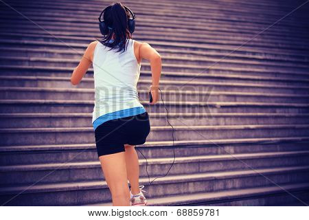Runner athlete running on stairs. listening to music in headphones from smart phone mp3 player smart