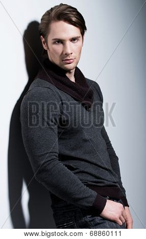 Fashion portrait of sexy young man in casual poses over wall with contrast shadows and looking at camera.