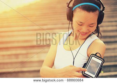 Runner athlete listening to music in headphones f