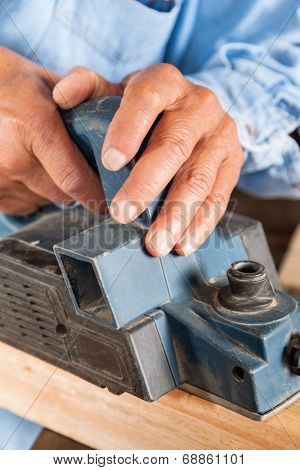 Closeup of senior carpenter's hands shaving wood with electric planer in workshop