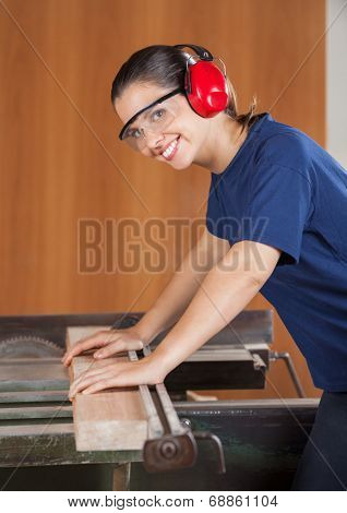 Side view portrait of happy female carpenter using tablesaw in workshop