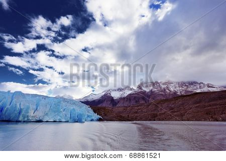 Chilean Patagonia. National Park Torres del Paine. Lake and Glacier Grey. The clouds covered the sun cold. Grey glacier moves down the water of the lake