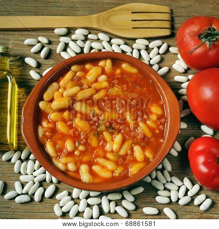 an earthenware bowl with potaje de judias, a spanish white beans stew, on a rustic wooden table with the ingredients to prepare it