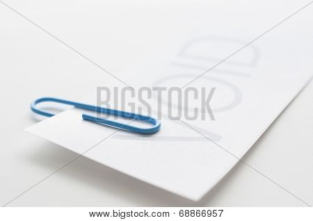 Void paper with blue paper clip on white background