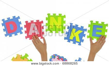 """Hands forming word """"Danke"""" with jigsaw puzzle pieces isolated"""