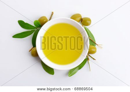 bowl of fresh olive oil and olive branches on white background