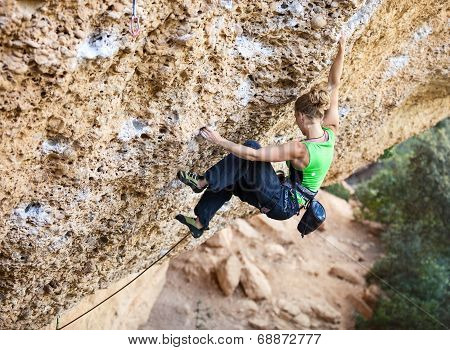 Young female rock climber on face of a cliff