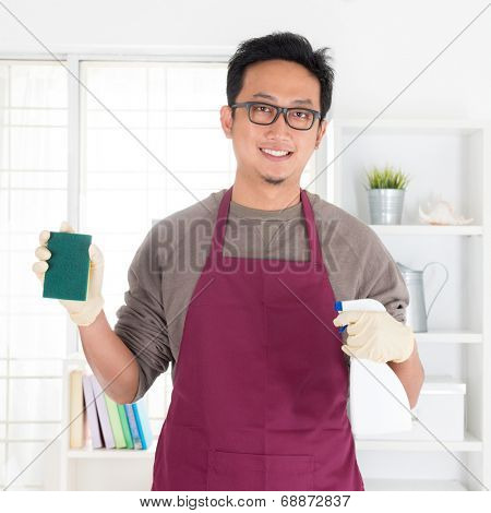 Asian man holding sponge and spray. House husband doing house chores, with interiors.