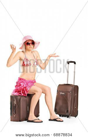 Uncertain female tourist sitting on her baggage isolated on white background