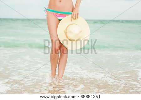 Girl wearing bikini and holding a straw hat posing at the sandy beach. Legs close-up