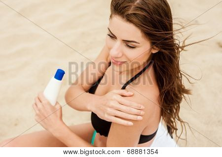 A smiling woman is applying sunblock on the beach, vintage-style photo.