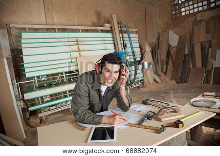 Portrait of happy carpenter working on blueprint while wearing ear protectors at table in workshop