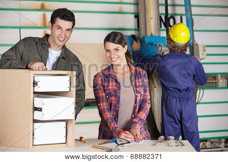 Portrait of confident male and female carpenters making cabinet in workshop