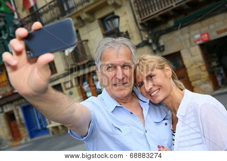 Senior tourists taking picture of themselves with smartphone