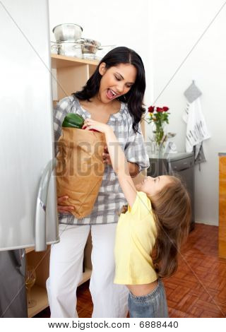 Blond Little Girl Unpacking Grocery Bag With Her Mother