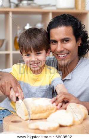 Smiling Father Helping His Son Cut Some Bread