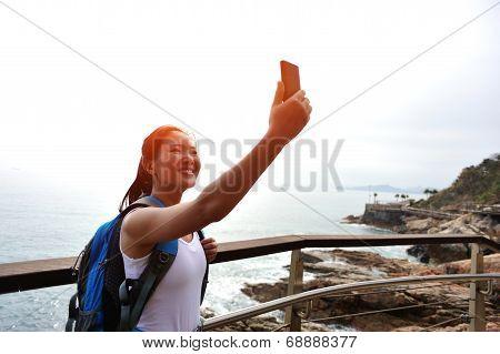 woman hiker taking self photo on sunrise seaside
