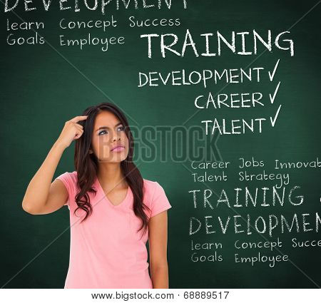 Pretty brunette thinking against green chalkboard with business buzzwords
