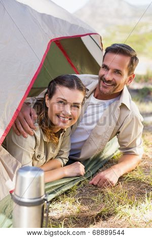Outdoorsy couple smiling at camera from inside their tent on a sunny day
