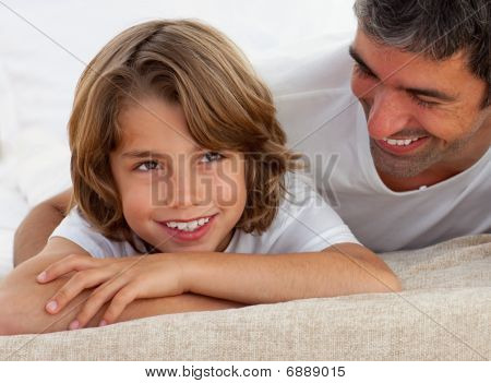 Cute Little Boy Having Fun With His Father Lying On Bed