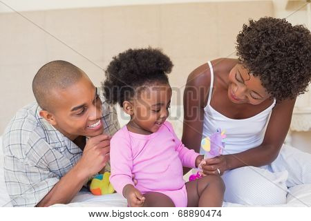 Happy parents playing with baby girl on bed together at home in the bedroom