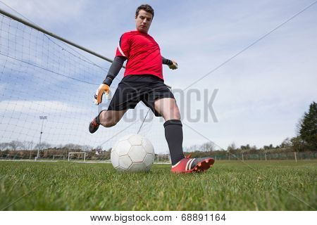 Goalkeeper in red kicking ball away from goal on a clear day