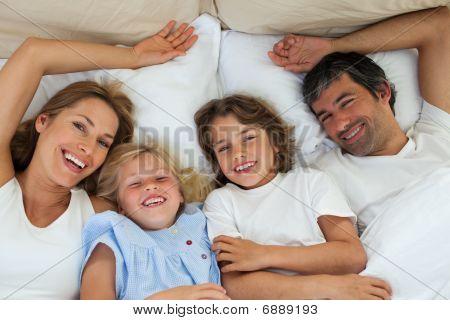Smiling Family Having Fun In The Bedroom