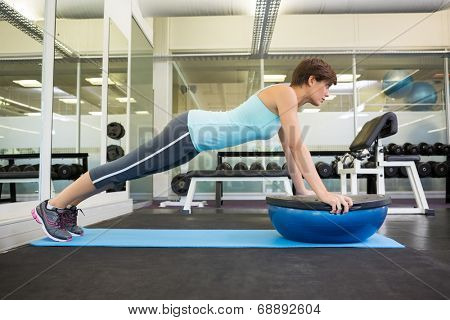 Fit brunette using bosu ball in plank position at the gym