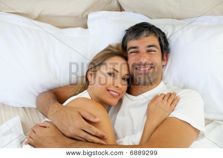 Smiling Couple Embracing Lying In Bed