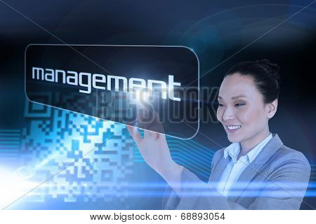 Businesswoman pointing to word management against shiny barcode on black background