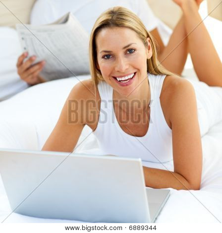 Smiling Woman Using A Laptop Lying On Bed