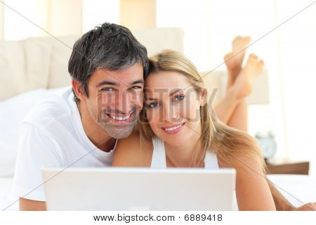 Enamoured Couple Using A Laptop Lying On Bed