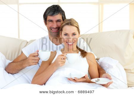 Affectionate Couple Drinking Coffee Lying In The Bed
