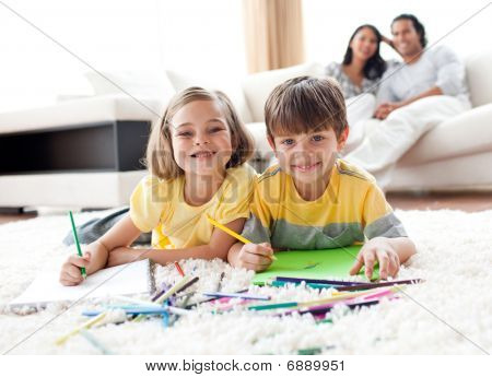 Portrait Of Cute Siblings Drawing Lying On The Floor