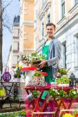 stock photo of viola  - Young handsome florist delivering palette of flowers or viola - JPG