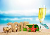 stock photo of champagne color  - Champagne and New year sign on sandy beach - JPG