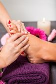 picture of pumice stone  - Woman having a pedicure treatment at a spa or beauty salon with the pedicurist massaging the soles of her feet with a pumice stone to cleanse dead skin and stimulate the tissue - JPG