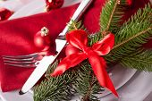 pic of christmas theme  - Red themed Christmas place setting with a colorful red napkin on white plates decorated with small red Xmas baubles and burning tea lights for a festive seasonal table